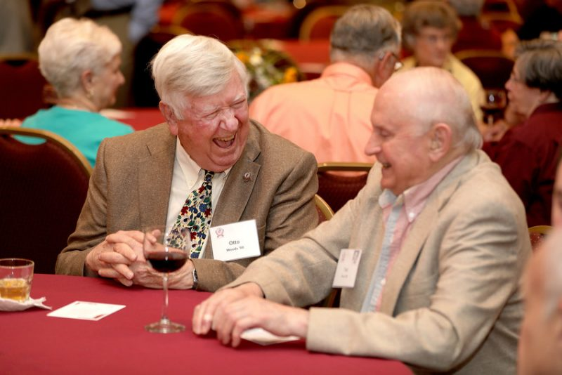 Two alumni laugh at a dinner at the Old Guard Reunion