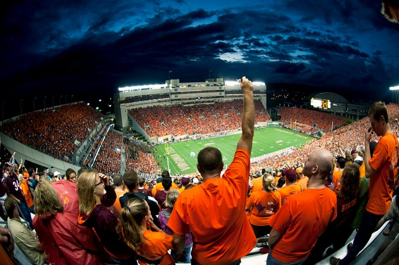Hokies cheering in the stands at Lane Stadium at night