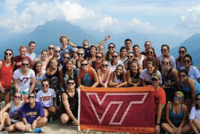 College of Pamplin study abroad student pose with a Virginia Tech flag