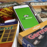image of travel books for countries arrayed across a table with a cell phone on top with the trip advisor logo on it