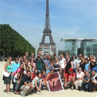 image of a group of students with a virginia tech flag in a park in paris france near the eiffel tower