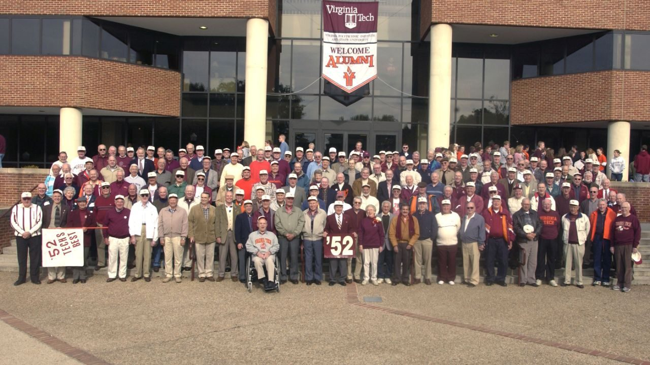 "alumni members of the class of 1952 arrayed on the steps of Squires Student Center with a banner behind them reading ""Welcome Alumni"""